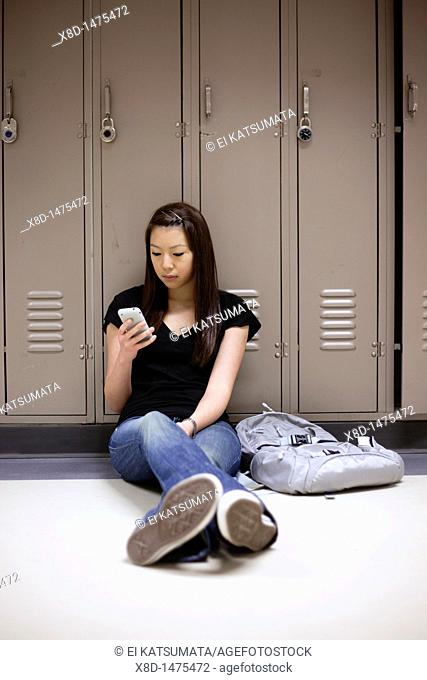 Young Asian woman texting on her smart phone while sitting on floor in school hallway