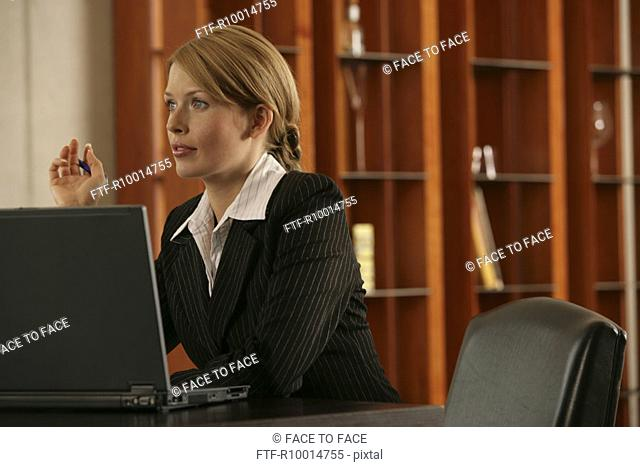 A blonde businesswoman with a laptop