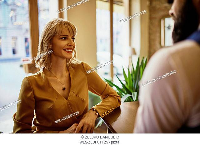 Elegant smiling woman with man in a bar