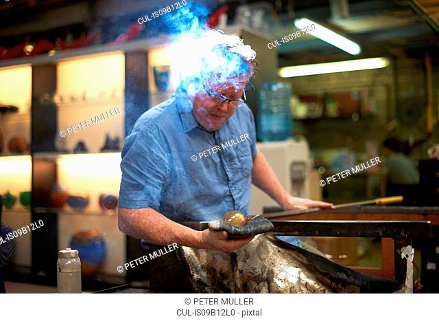 Glassblower in workshop forming molten glass on blowpipe