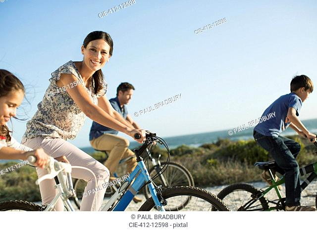 Family riding bicycles on beach