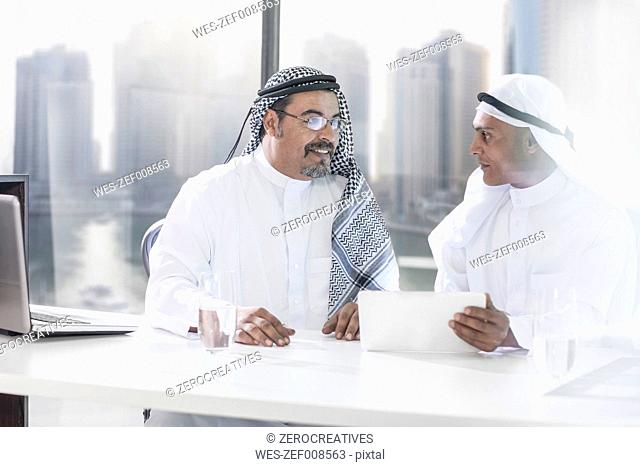 Two Middle Eastern businessmen sitting office, looking at digital tablet