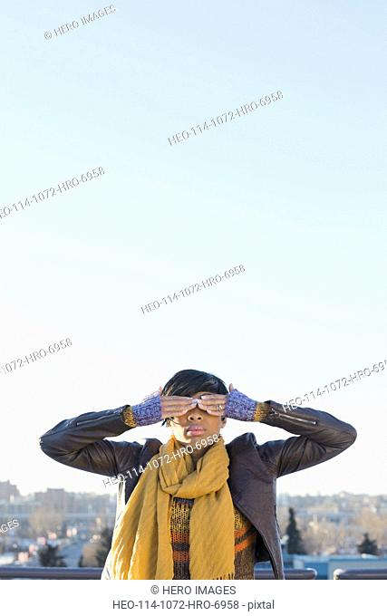 Woman covering eyes with two hands outdoors