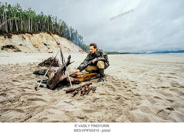 Man collecting firewood on the beach, preparing campfire