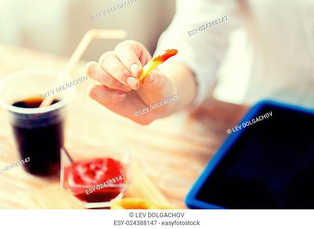 fast food, people and unhealthy eating concept - close up of woman dipping french fries into ketchup and drinking cola on wooden table