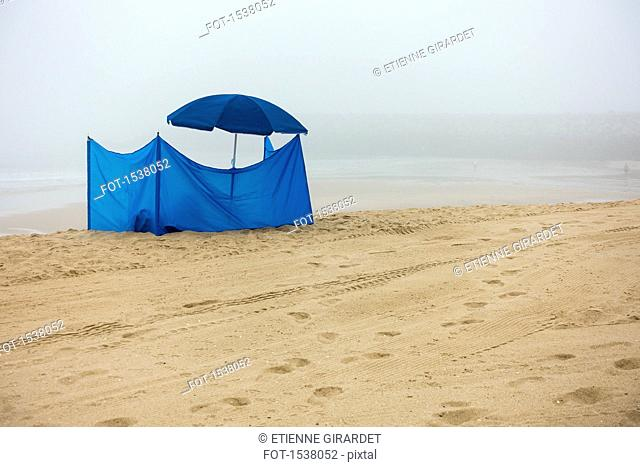 Blue tent and parasol at beach against sky during foggy weather