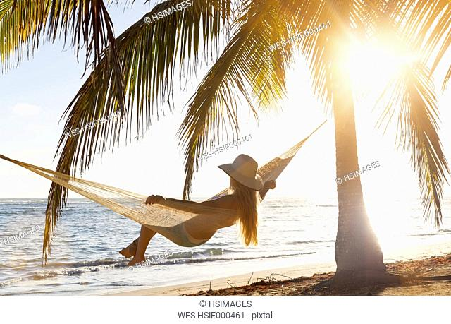 Dominican Rebublic, Young woman in hammock looking out over tropical beach