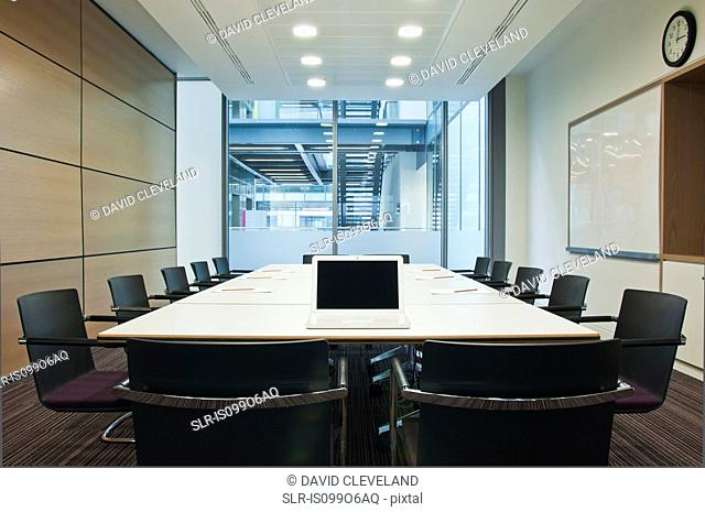 Laptop on conference table in empty office block