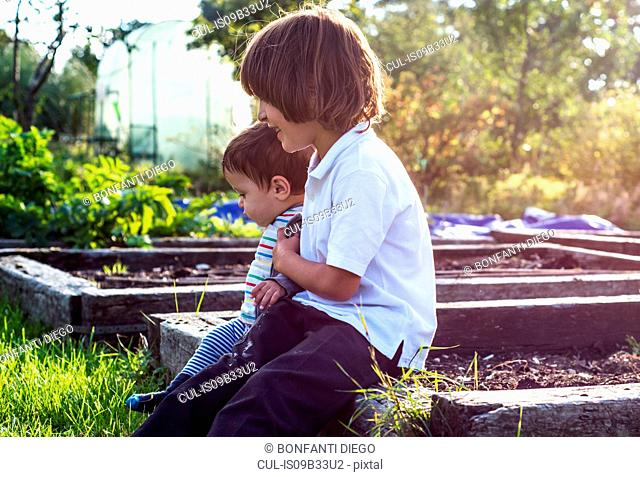 Boy and his baby brother sitting together in sunlit rural garden