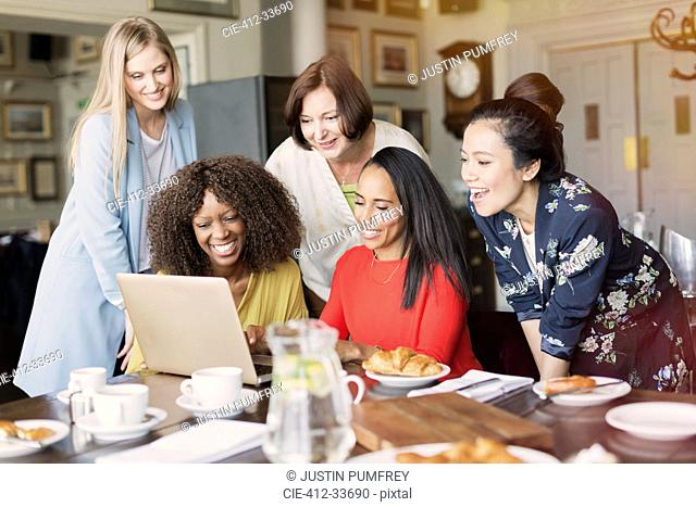 Smiling women friends using laptop at restaurant table