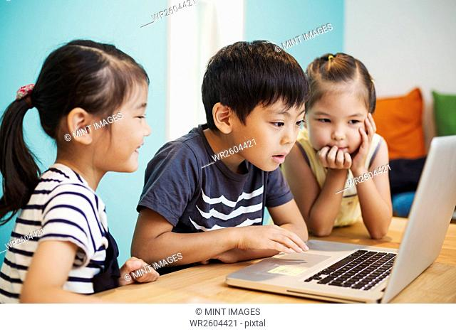 Three children using a laptop, two girls and a boy