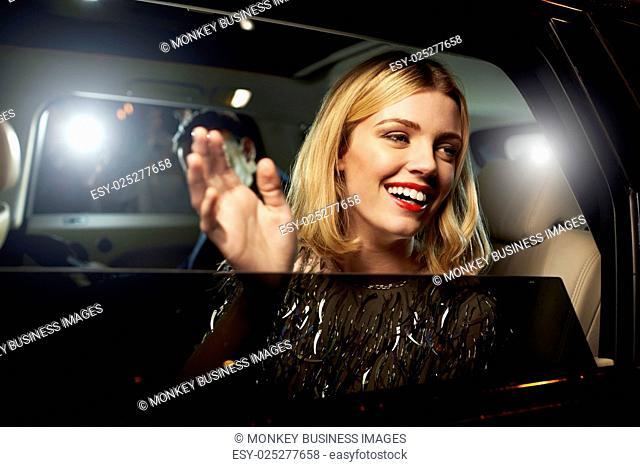 Glamorous woman waving through the window of a limousine