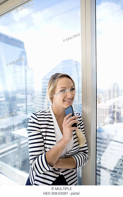 Smiling businesswoman holding cell phone at urban office window