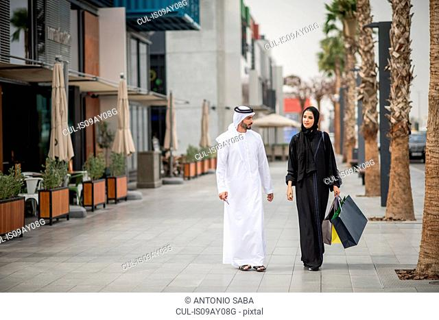 Middle eastern shopping couple wearing traditional clothing carrying shopping bags, Dubai, United Arab Emirates
