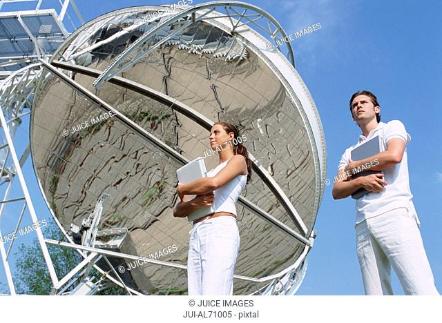 Low angle view of two scientist holding laptops in front of solar mirror against blue sky, Stuttgart, Germany