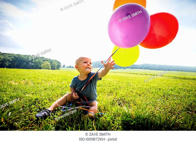 Baby boy sitting in rural field with bunch of colourful balloons