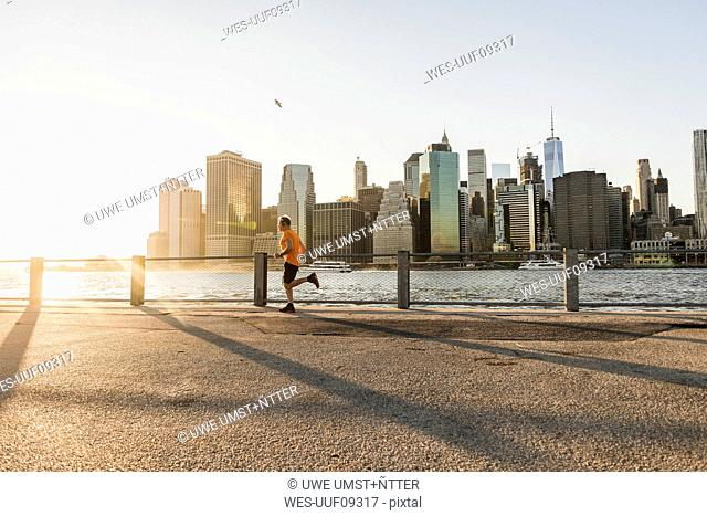 USA, Brooklyn, man jogging in front of Manhattan skyline in the evening