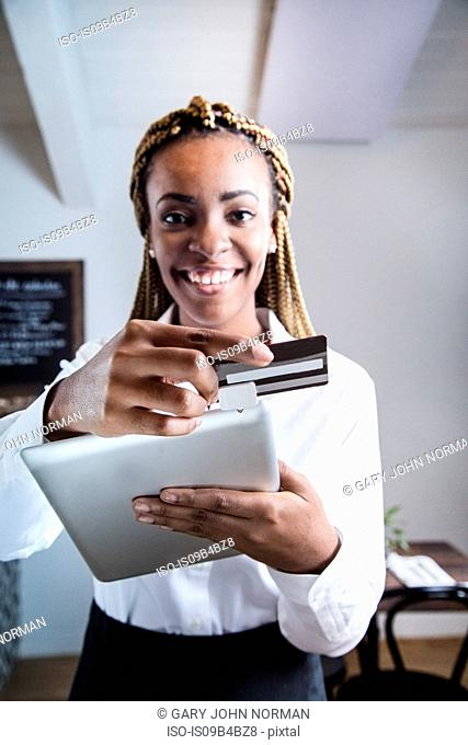 Portrait of waiter in restaurant, using digital tablet to take payment