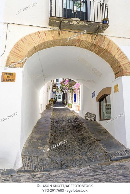 An arch passageway through a whitewashed building along Carrer des Call known for its herringbone rastell cobble pavement, Cadaqués, Catalonia, Spain