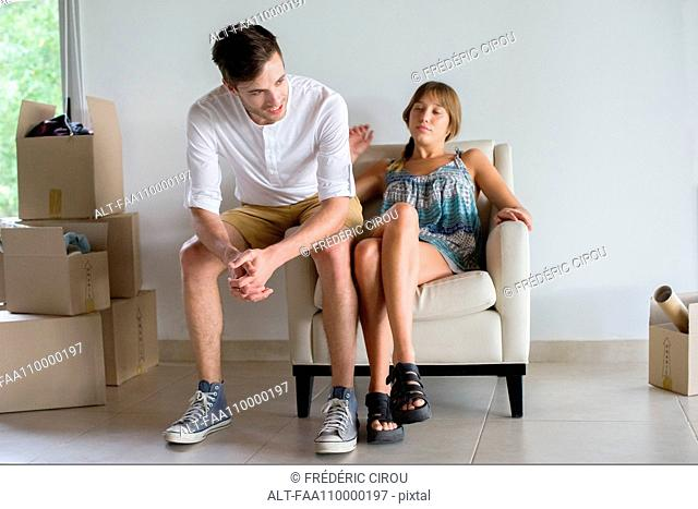 Couple taking break from unpacking in new house