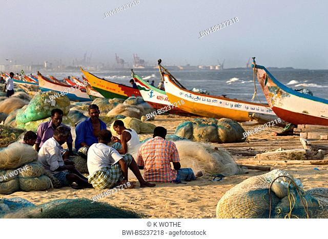 fishermen sitting on sand beach among their boats and nets, India, Tamil Nadu, Marina Beach, Chennai