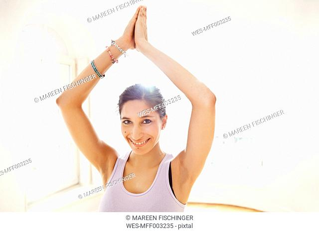 Smiling woman holding tree pose in sunny yoga studio