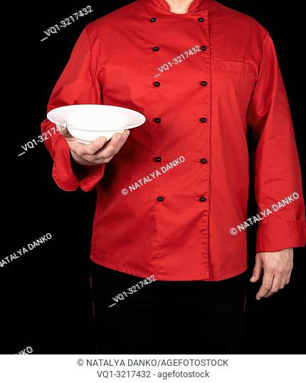 chef in red uniform holds in his right hand a round white plate for soup, black background