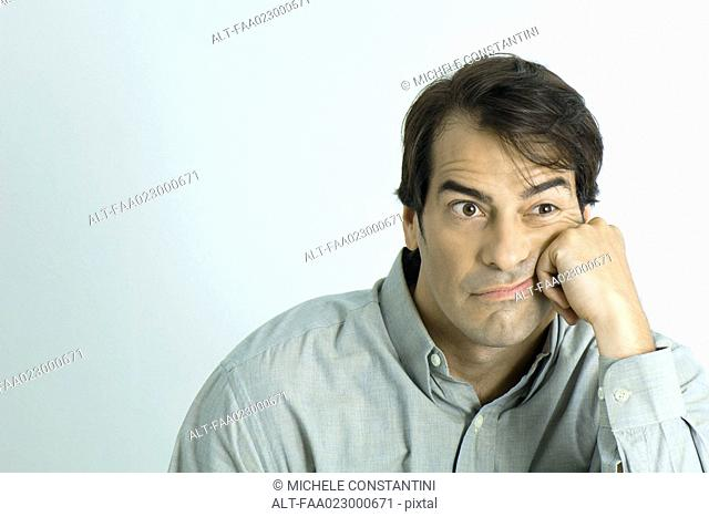 Man leaning face against hand, looking grumpy