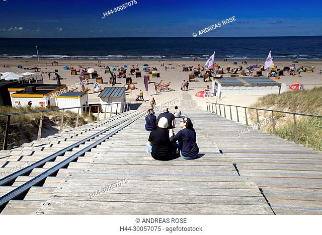 People are sitting at the wooden stairs exit to the beach of Egmond, North Sea, Holland, Netherlands