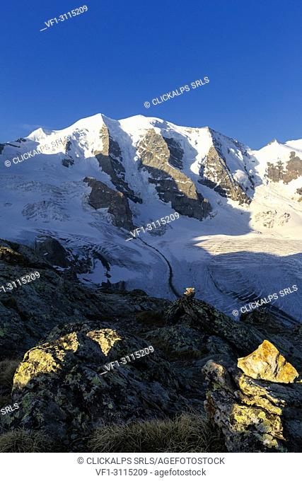 First sunlight illuminates rocks with Palù Peaks and Vedret Pers Glacier in the background. Diavolezza Refuge, Bernina Pass, Engadin, Graubünden, Switzerland