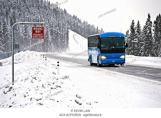 Wrong way sign and tour bus on Trans-Canada Highway in winter conditions near Lake Louise, Banff, Albert, Canada
