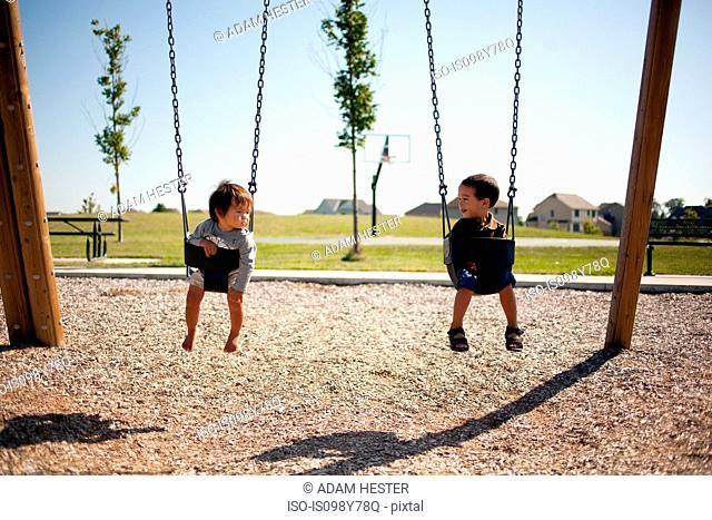 Two boys sitting in swings