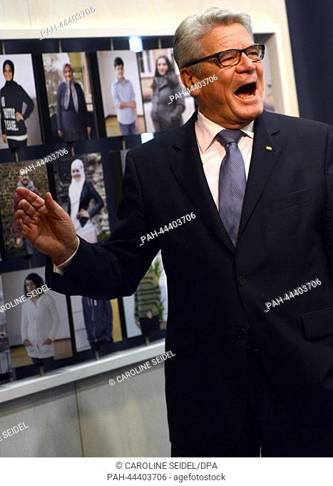 German President Joachim Gauck smiles during a tour of the exhibition at the Anette-von-Droste-Huelshoff-Gymnasium in Muenster, Germany, 28 November 2013