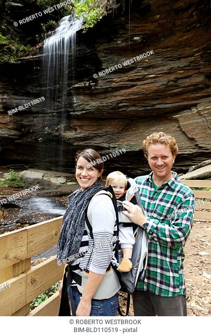 Caucasian family smiling by waterfall