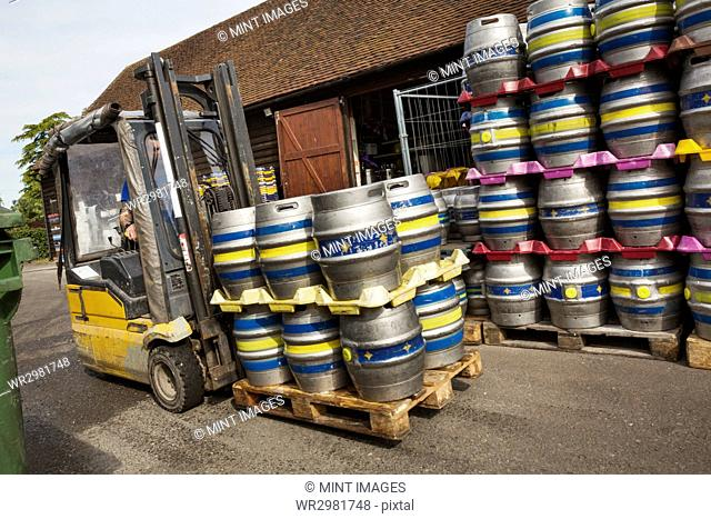 Stacks of metal beer cags on a forklift truck in a brewery