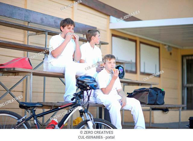 Three boys sitting on bleachers wearing cricket clothes