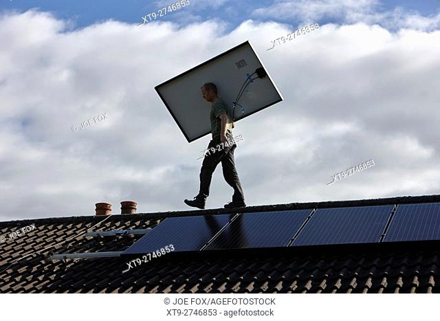man installing rooftop solar panel array in a domestic solar panel installation in the uk