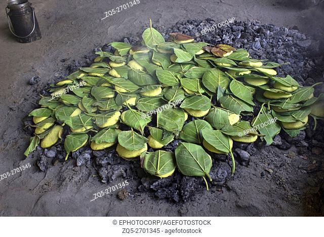 Dal paniya a common pulse dish on charcoal and covered with leaves. Madhya Pradesh, India