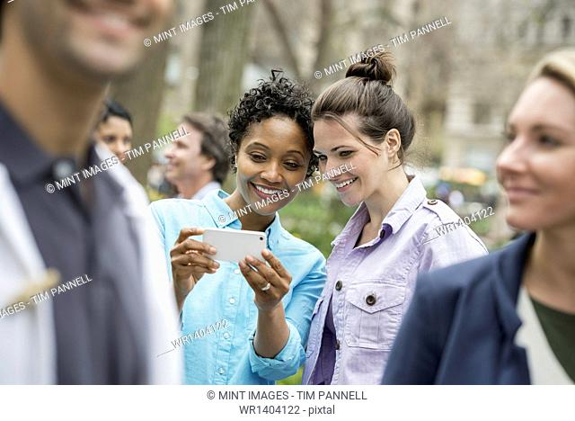 People outdoors in the city in spring time. New York City park. Two women in a group of friends, looking at a cell phone and smiling