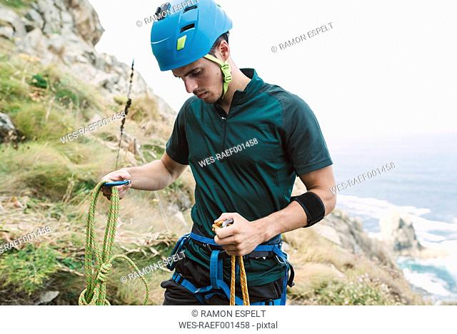 Young man preparing climbing equipment