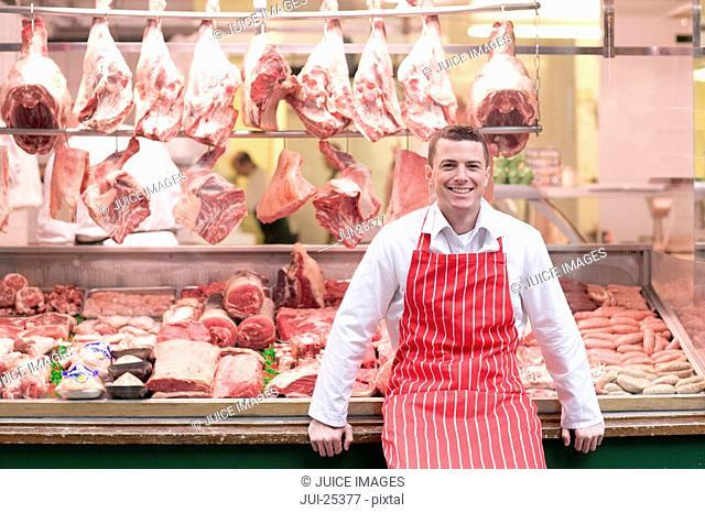 Butcher standing in front of butcher shop window