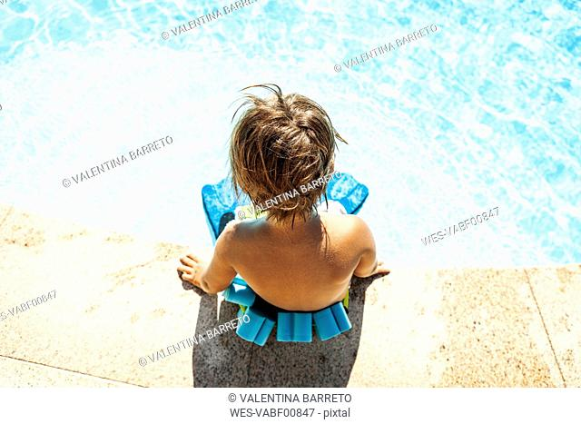 Back view of little boy with floating belt sitting at pool edge