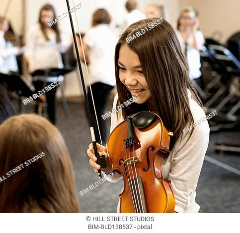 Caucasian student playing violin in music class
