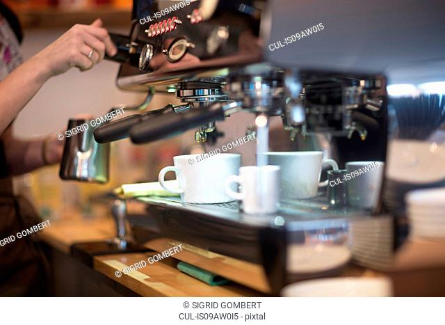 Cropped shot of waitress's using coffee machine in cafe