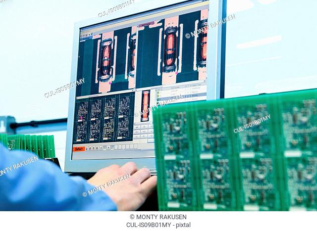 Worker testing circuit boards in circuit board assembly factory, close up