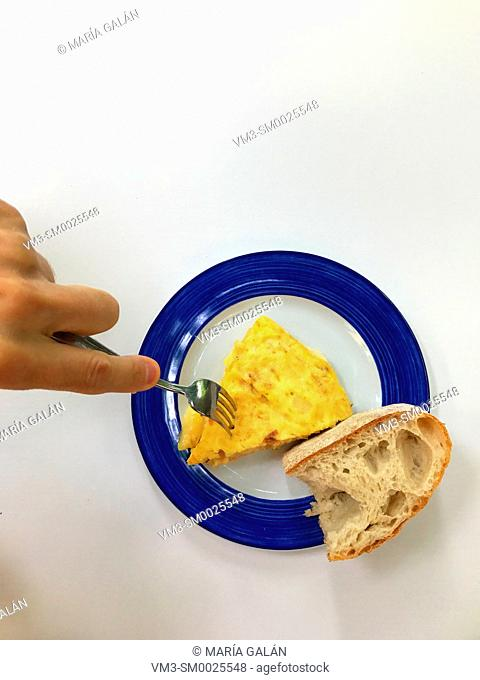 Hand taking a piece of Spanish omelet
