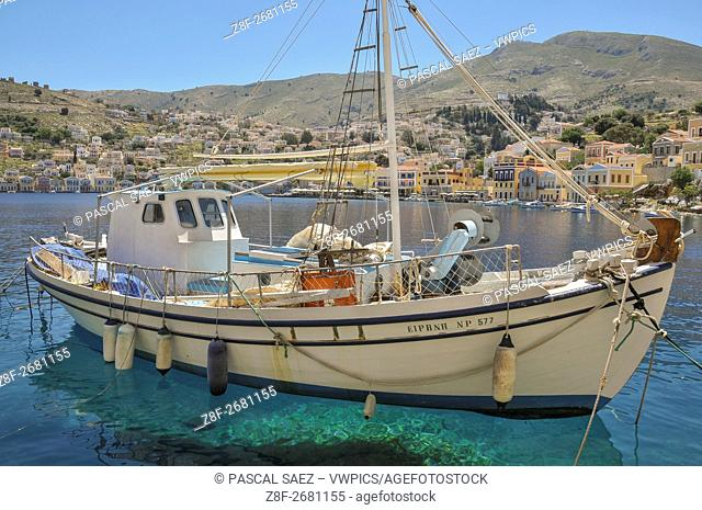 A small sailing yacht is moored along the seafront of Symi Town, on the island of Symi, part of the Dodecanese island chain