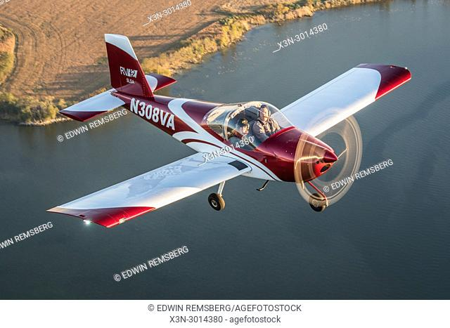 Male pilot operating blue Vans RV-12 light sport aircraft with female photographer flying over the Chesapeake Bay, Stevensville, Maryland, USA