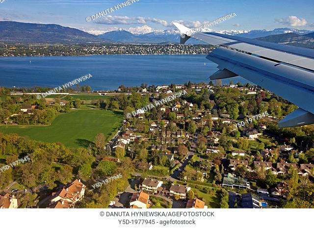 plane coming to landing at Geneva airport, Lake Geneva and Alps in the background, Switzerland