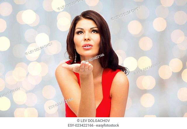 people, holidays and gesture concept - beautiful sexy woman in red dress sending blow kiss over holidays lights background